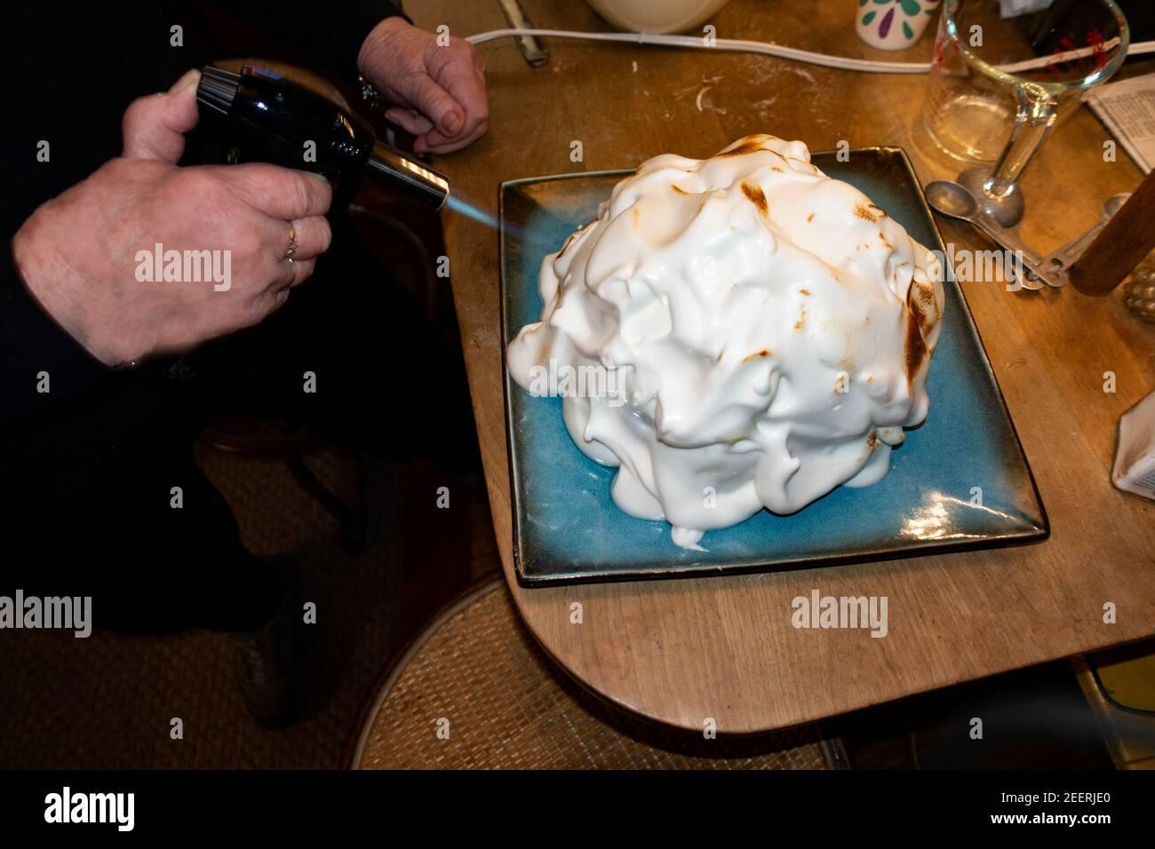Mujer usando una antorcha de cocina para pulir el merengue en una Alaska al horno. St Paul Minnesota MN EE.UU Foto de stock