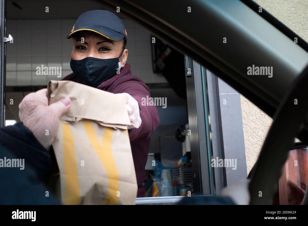 El trabajador del servicio de comida de McDonald's enmascaró la entrega de alimentos al cliente en el coche durante la pandemia de COVID-19. St Paul Minnesota MN EE.UU Foto de stock