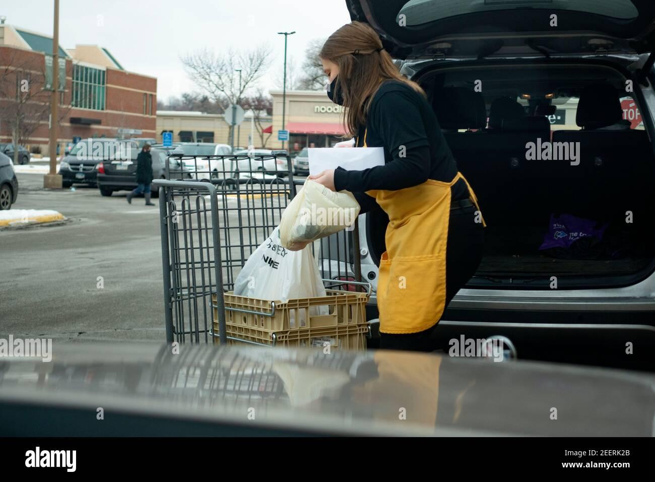Lunds & Byerlys Supermarket comprador enmascarado entrega de comestibles al vehículo del cliente durante Covid Pandemic. St Paul Minnesota MN EE.UU Foto de stock