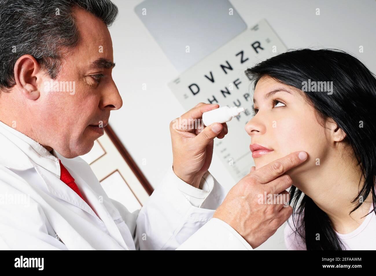 Perfil lateral de un médico masculino que pone gotas para los ojos Un ojo womanŽs joven Foto de stock