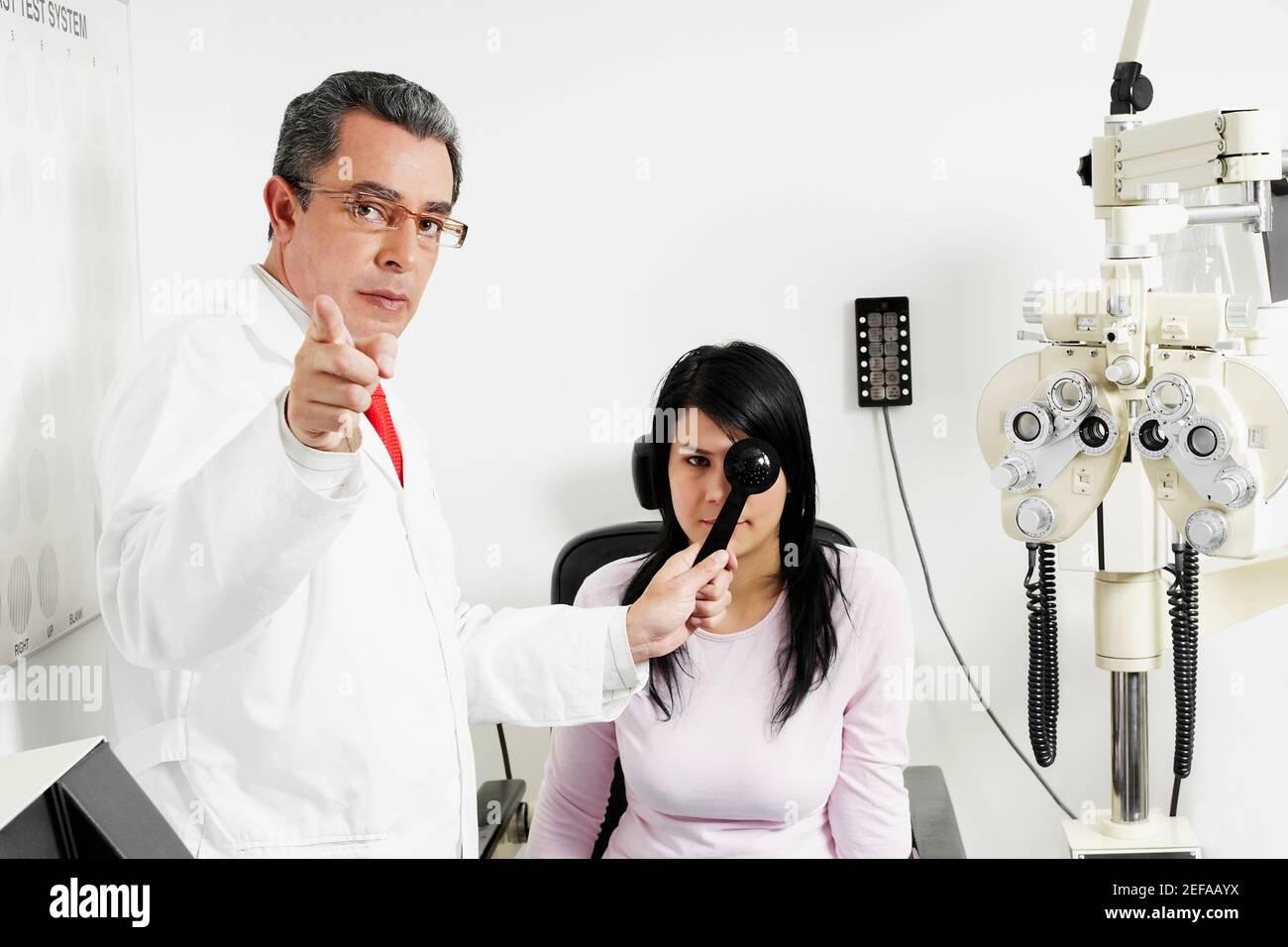 Retrato de un médico masculino que examina un ojo womanŽs joven Foto de stock
