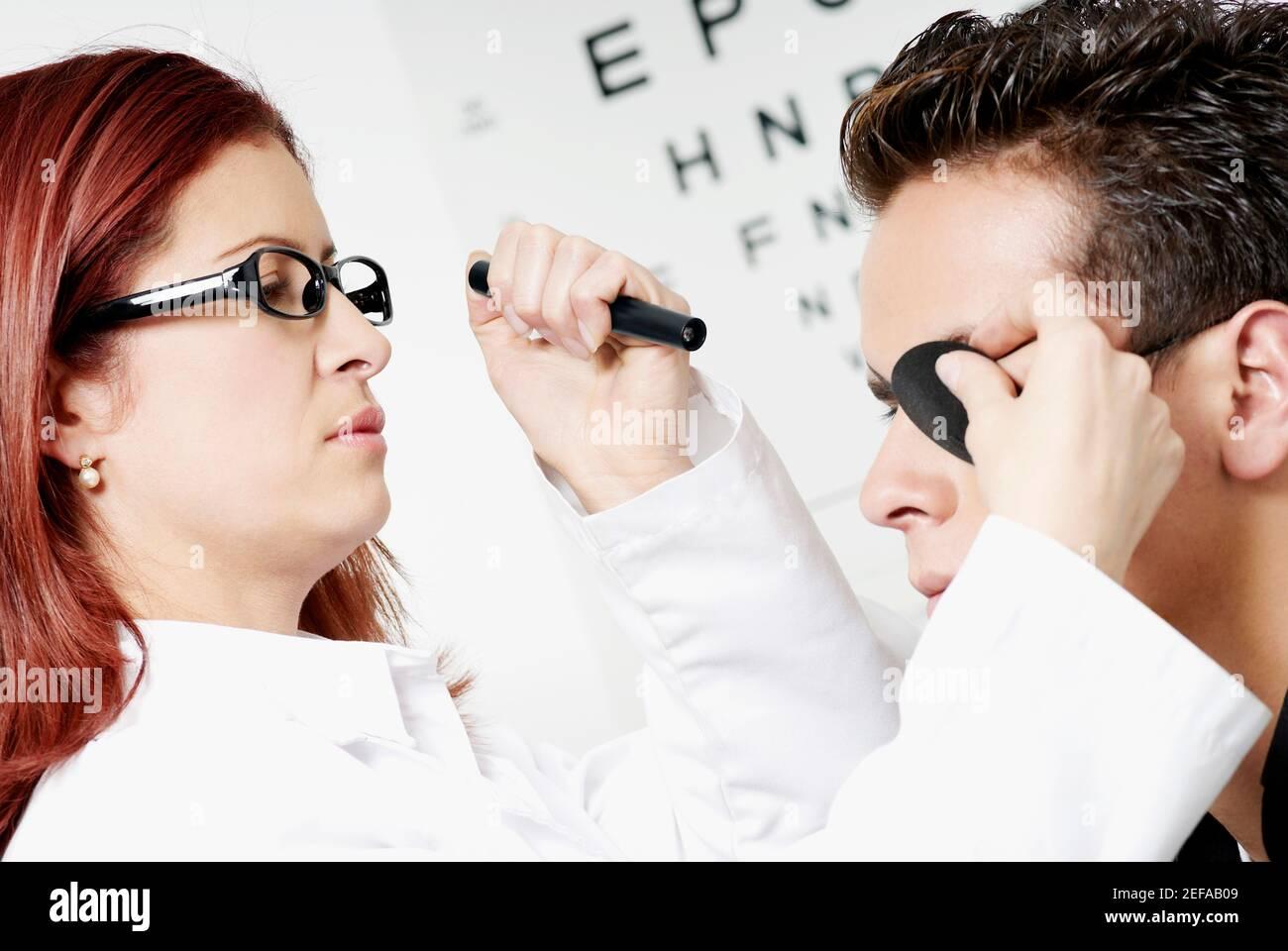 Primer plano de un optometrista femenino que examina los ojos de un joven hombre Foto de stock