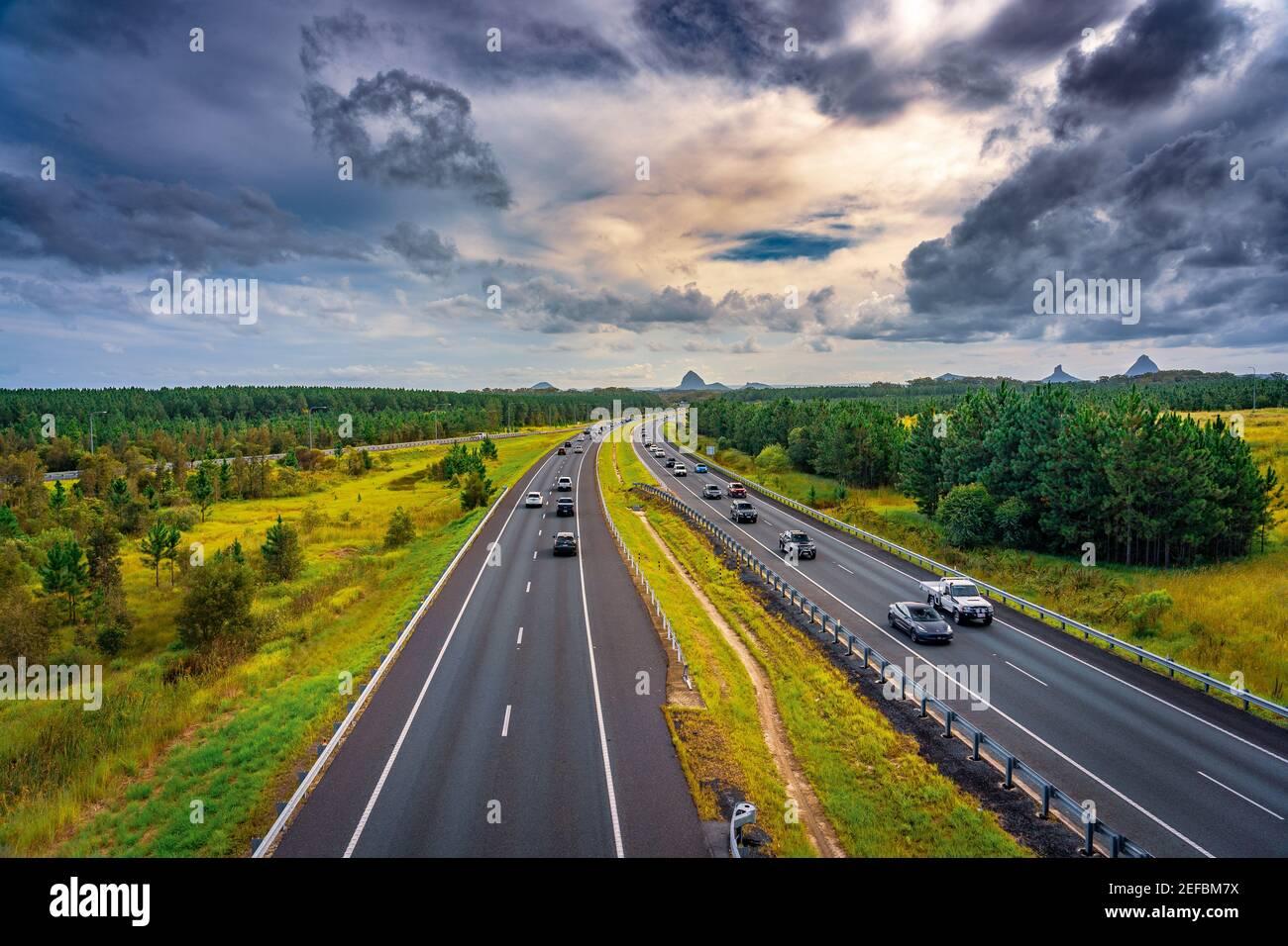 Queensland, Australia - Autos que se mueven a lo largo de Bruce Hwy con las montañas Glass House en el fondo Foto de stock