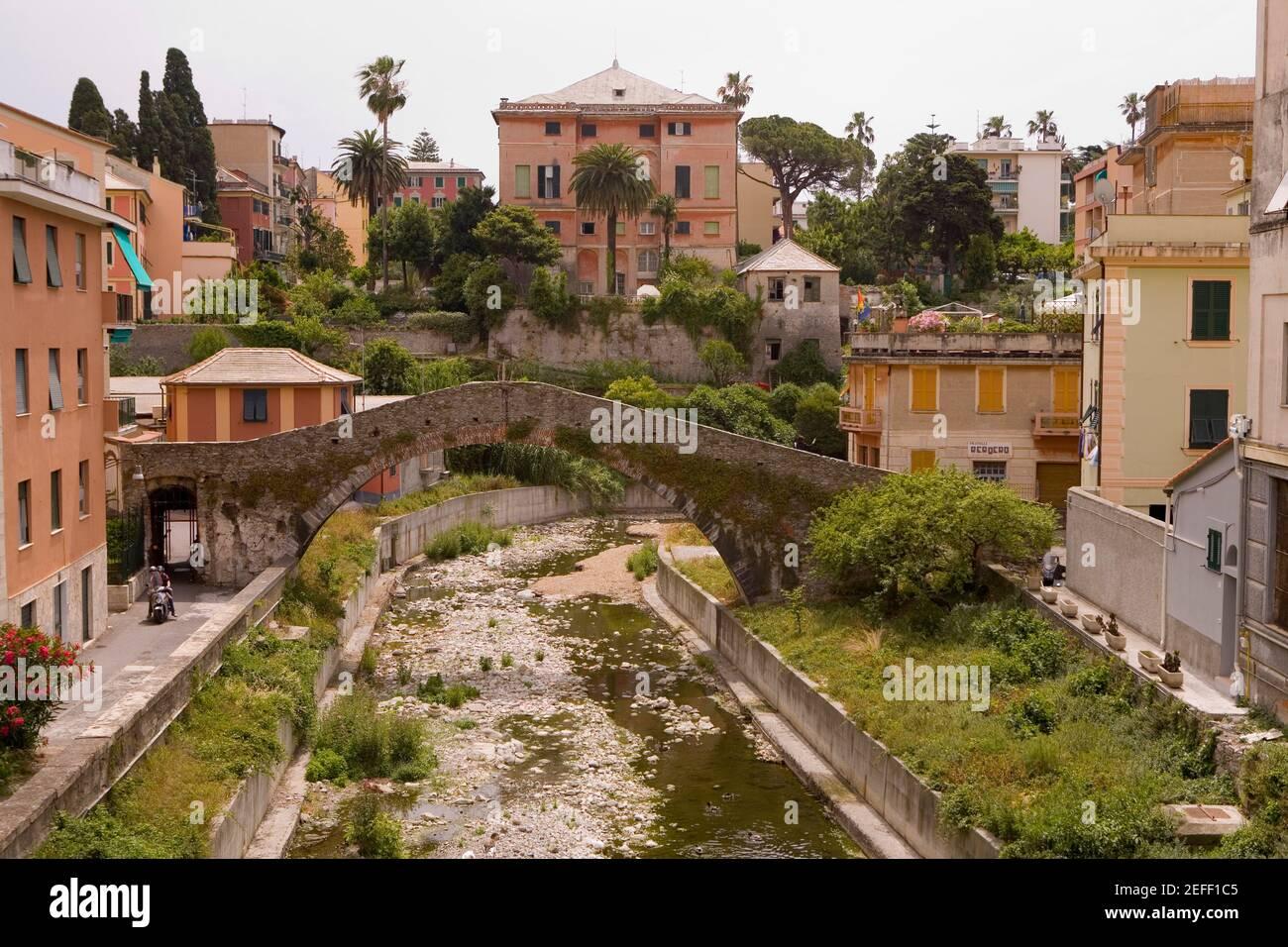 Puente arco cerca de edificios, provincia de Génova, Liguria, Italia Foto de stock