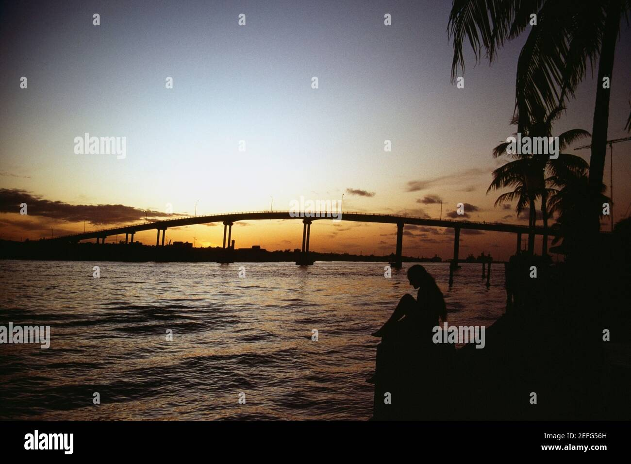Tranquilo paisaje marino y un puente que se perfila contra el cielo al atardecer, Grand Bahamas, Bahamas Foto de stock