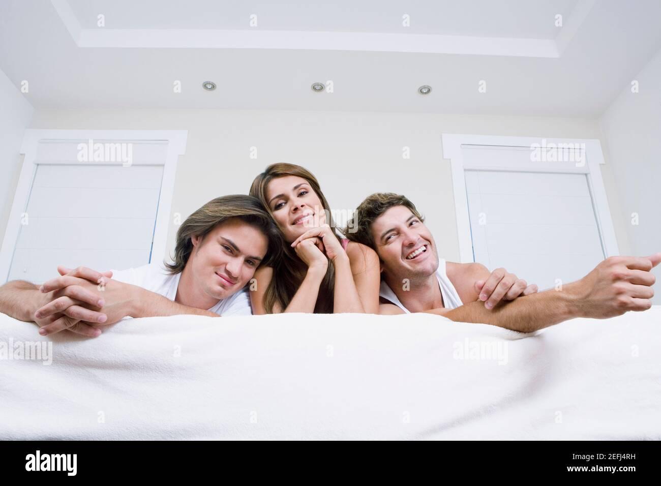 Vista de ángulo bajo de una joven que se encuentra entre dos hombres en la cama Foto de stock