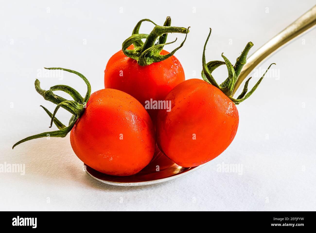 Primer plano de tres tomates rojos en una cuchara sobre un mantel blanco, Londres, Reino Unido Foto de stock