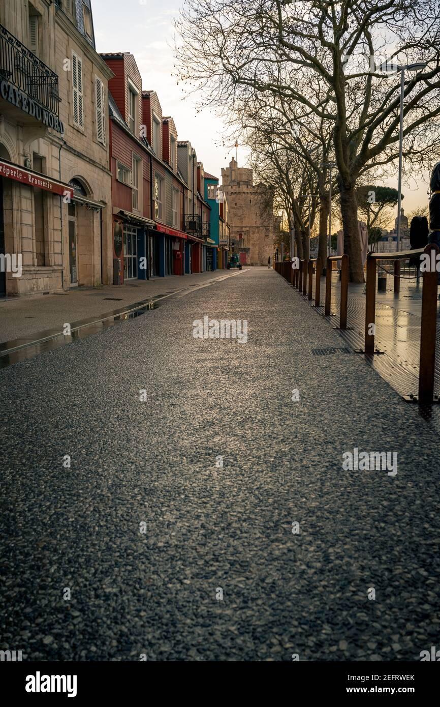Calle vacía por la noche en la rochelle, Francia. Torre de San Nicolás en el fondo Foto de stock