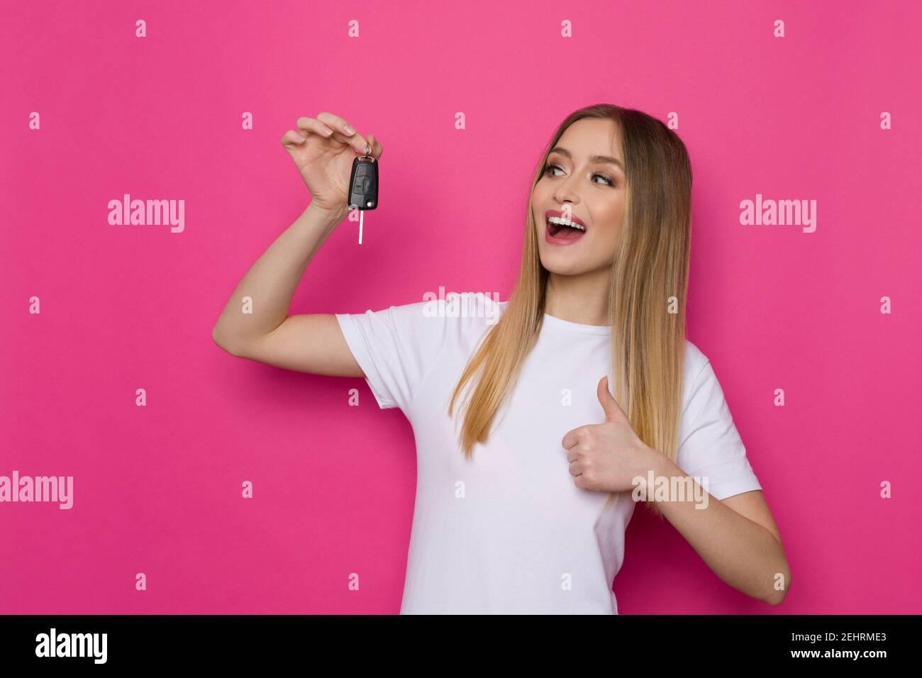 Mujer joven feliz en camisa blanca está sosteniendo la llave del coche, mostrando el pulgar hacia arriba y hablando. Estudio de cintura arriba sobre fondo rosa. Foto de stock