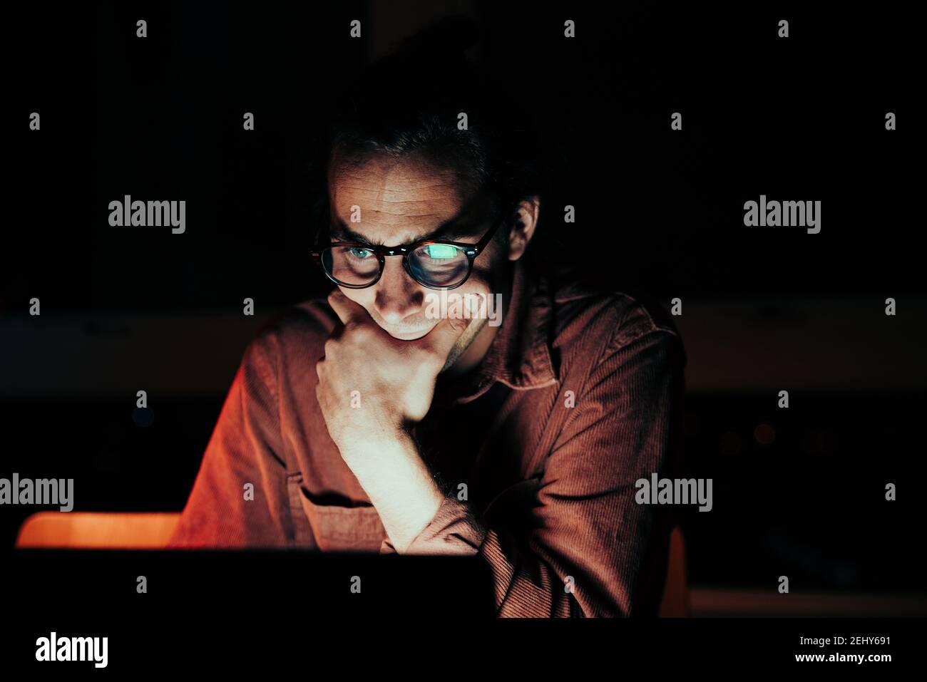 Close up caucásico hombre independiente leer fuera de la laptop trabajando tarde por la noche Foto de stock