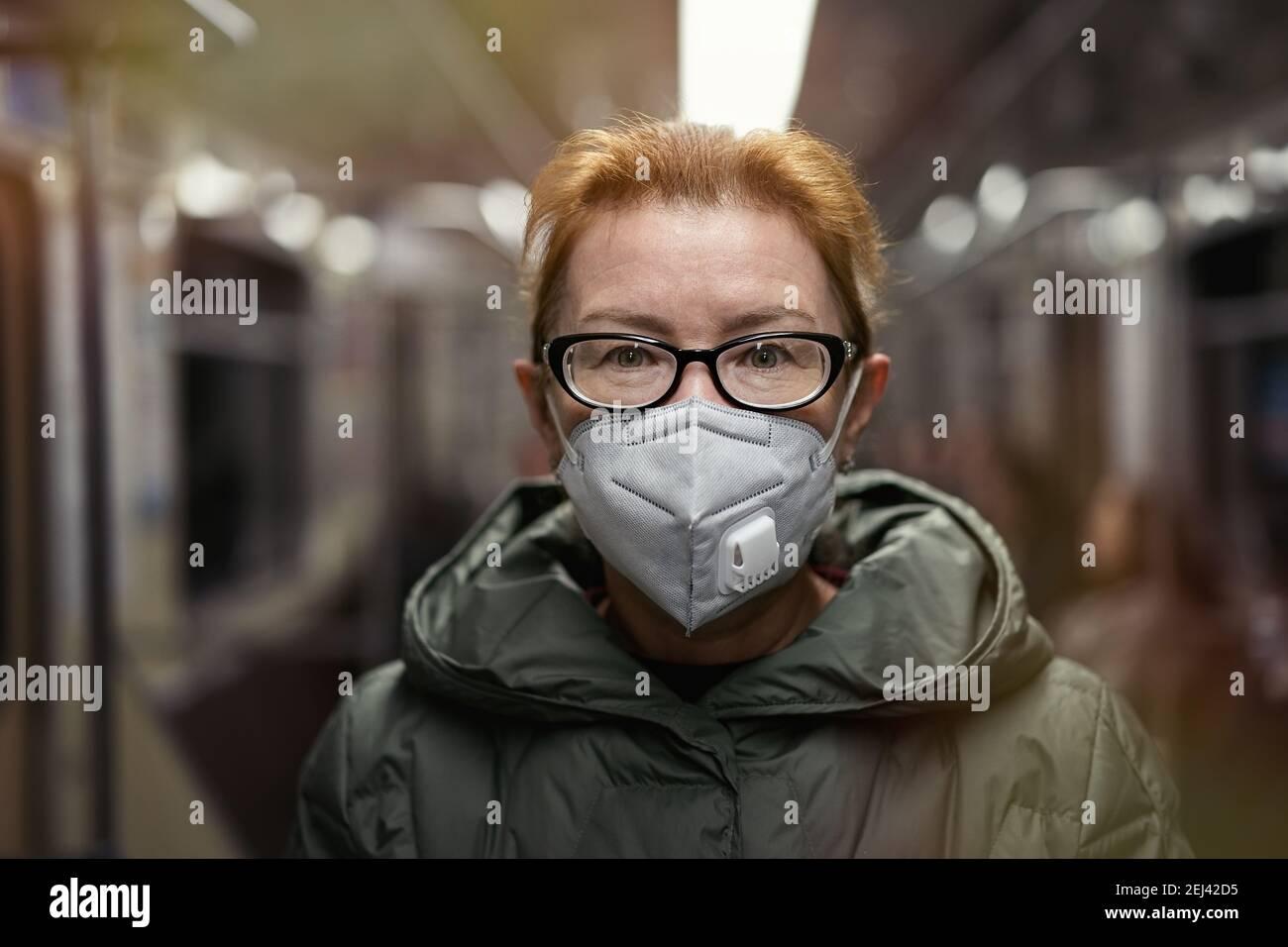 Retrato mujer madura en máscara de respiración viajando en tren subterráneo. Concepto de nueva realidad vital durante la pandemia de COVID 19 Foto de stock