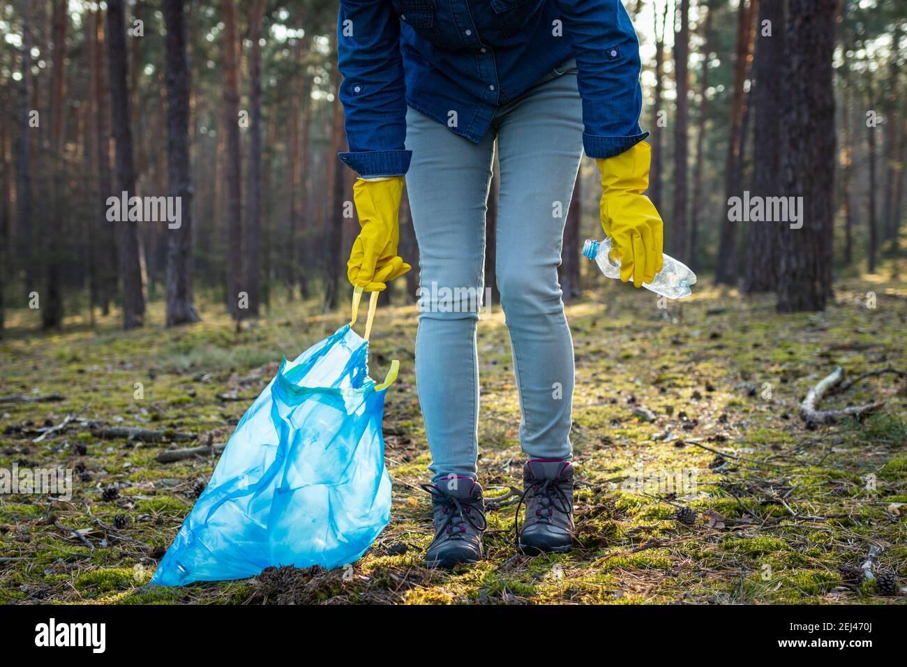 Voluntario está limpiando el bosque de la contaminación plástica. ¡haga nuestro planeta verde y limpio! Concepto de conservación ambiental Foto de stock