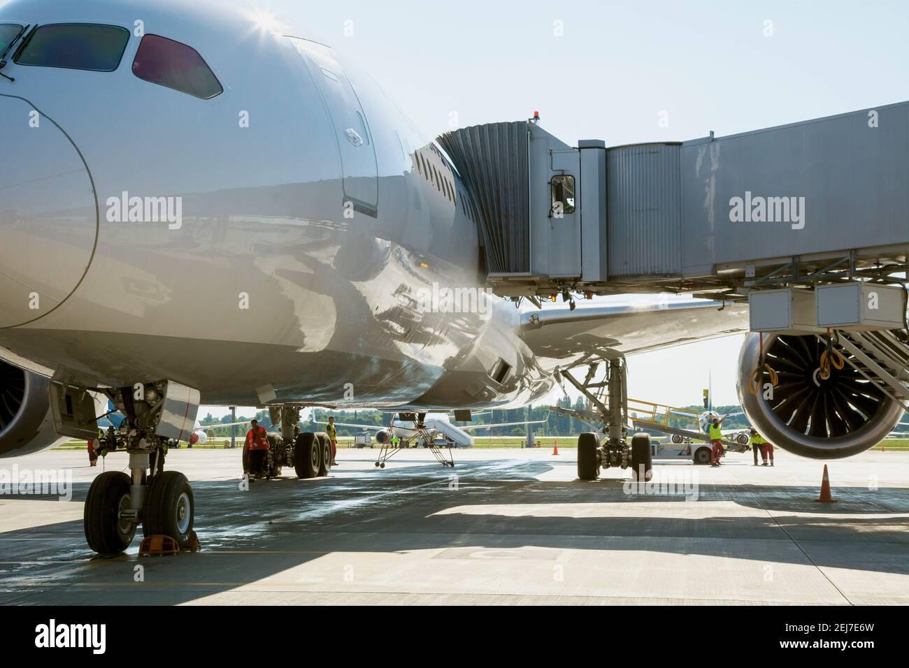 Embarque de pasajeros en el avión a través del puente de embarque. El avión aterriza en el aeropuerto internacional. Cargando equipaje. Avión blanco. Terminal Foto de stock