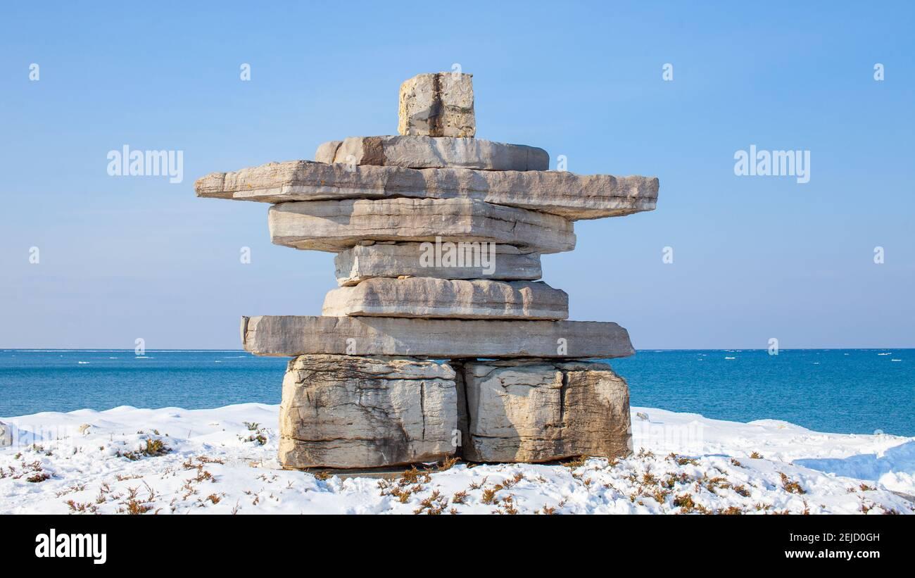 Un gigante de Inukshuk se encuentra con vistas a la Bahía Georgiana en el Parque Sunset Point de Collingwood. Un monumento en la comunidad, honrando a un hombre local. Foto de stock