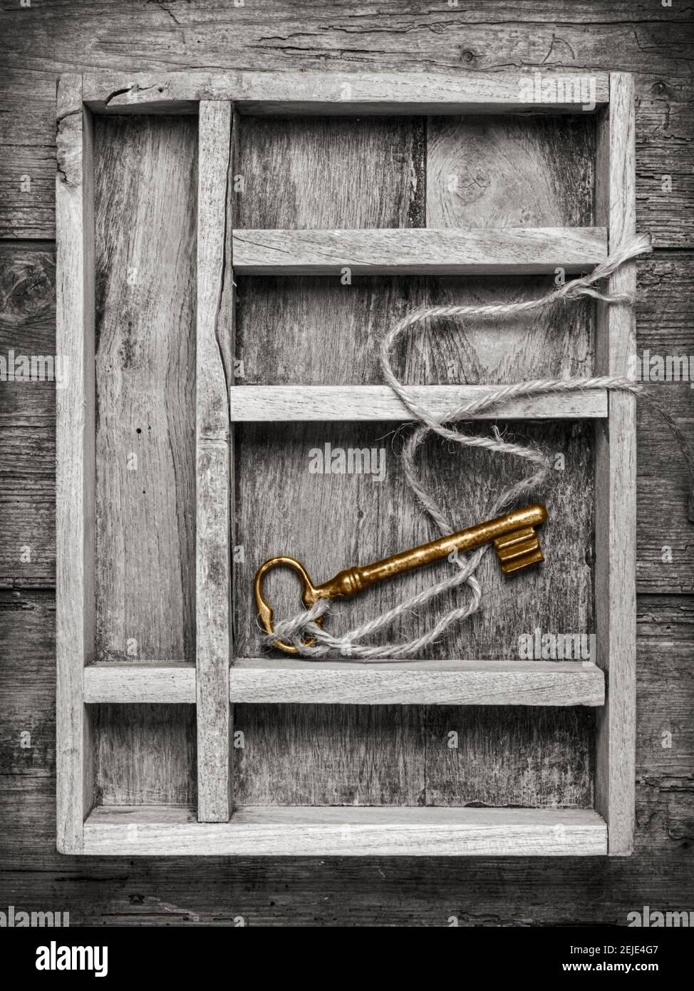 llave dorada vintage con cuerda en compartimento de caja de madera, vista superior Foto de stock