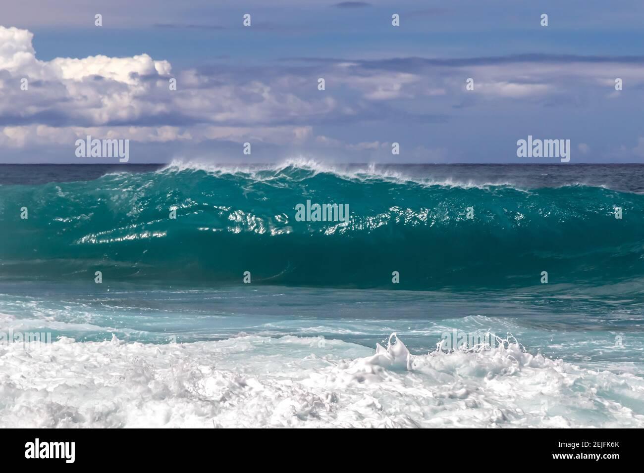 Ondulado en la playa hawaiana. Aerosol volando de vuelta en la parte superior de la ola. Espuma de la onda anterior en primer plano. Aerosol blanco de mar tirado al aire. Foto de stock