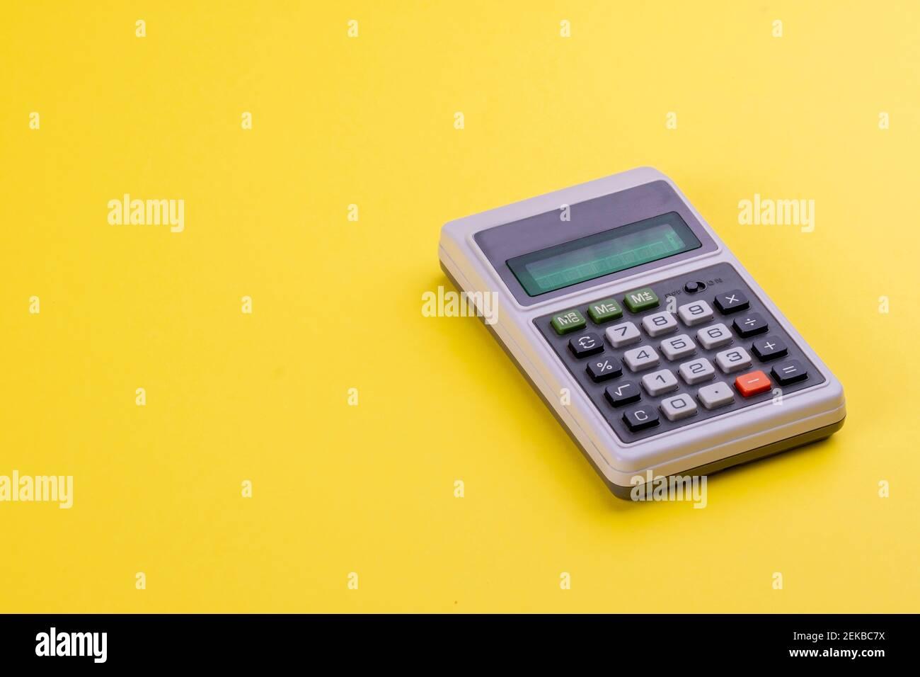 Objetos retro en negocios y educación. Una calculadora de época con pantalla digital y botones numéricos sobre fondo amarillo Pantone 2021. Contando Foto de stock