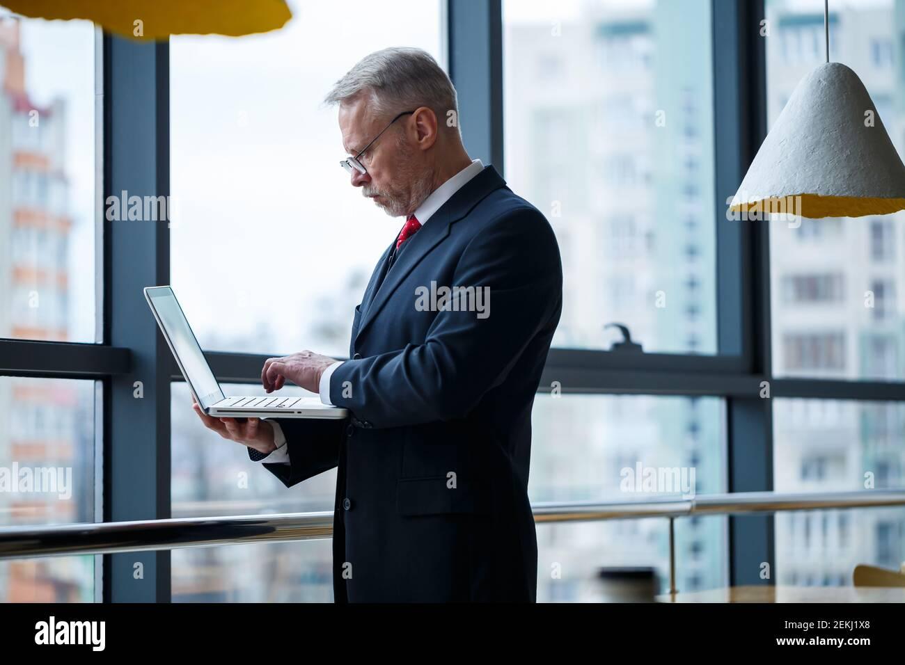El director ejecutivo sonriente y feliz piensa en el éxito de su desarrollo profesional mientras se mantiene con un ordenador portátil en su oficina cerca del telón de fondo de una victoria Foto de stock