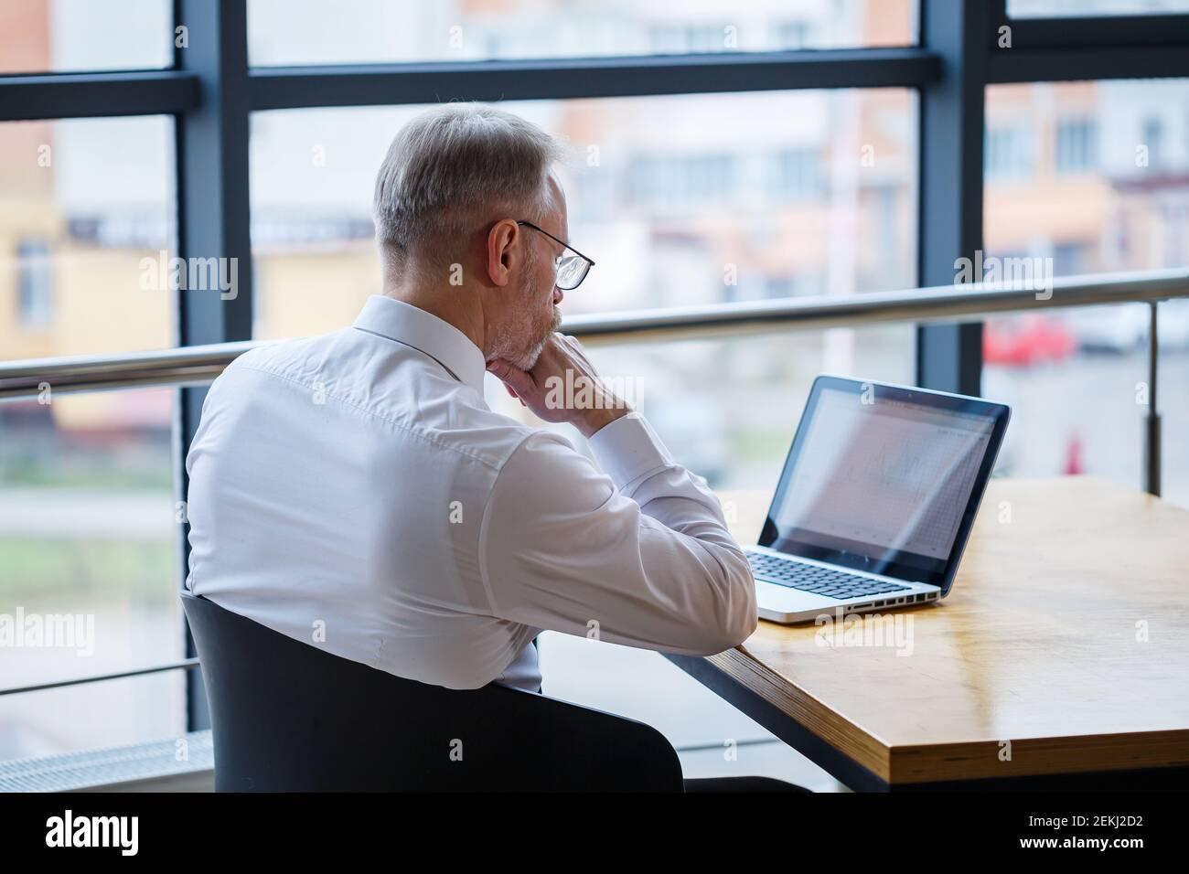 Hombre freelancer está trabajando en un café en un nuevo proyecto de negocios. Se sienta en una ventana grande en la mesa. Mira a una pantalla de portátil con una taza de café Foto de stock