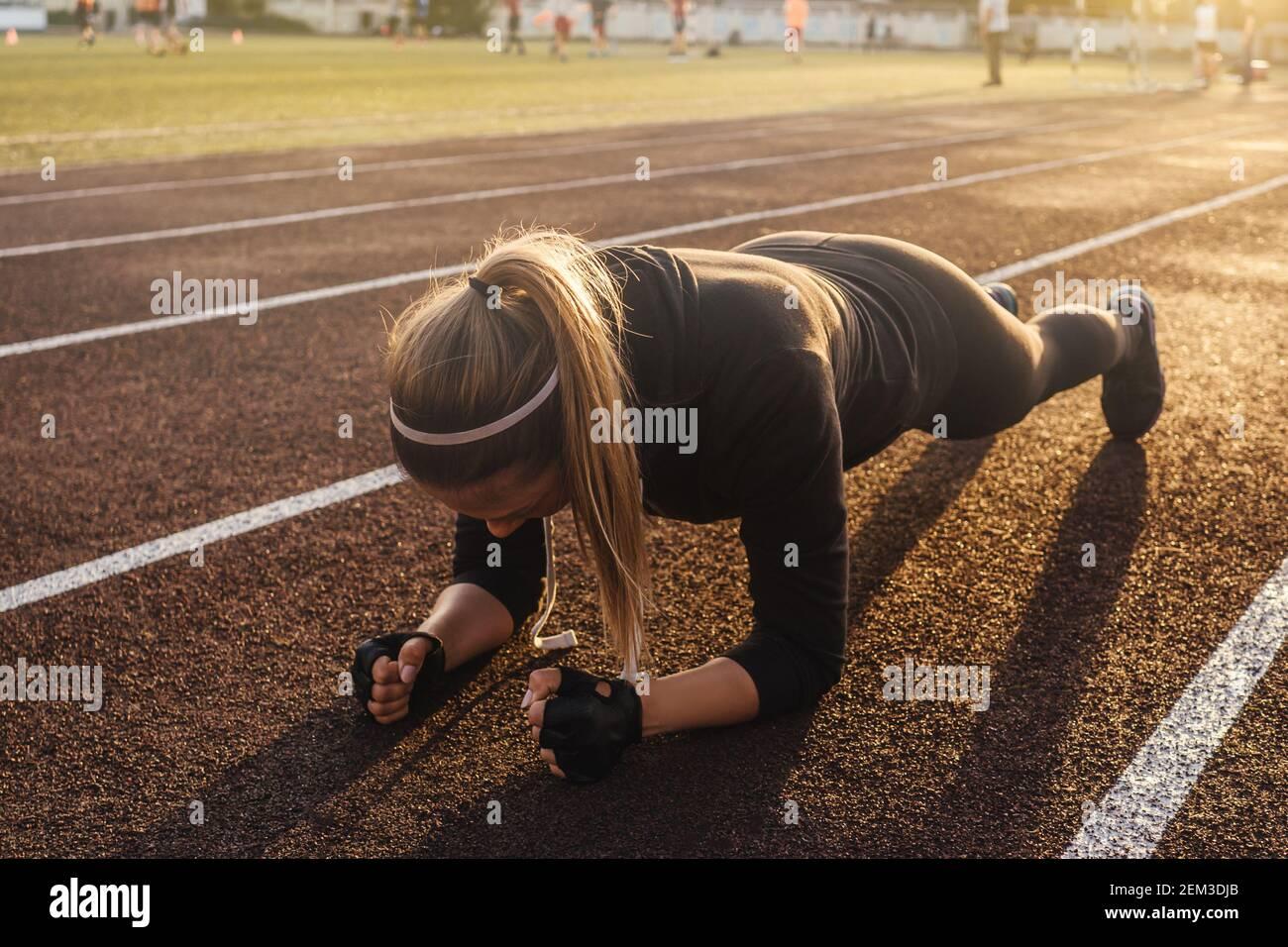 Joven mujer atlética haciendo ejercicio de tabla en pista de correr. Luz de puesta de sol sobre fondo, hermosa perspectiva. Foto de stock