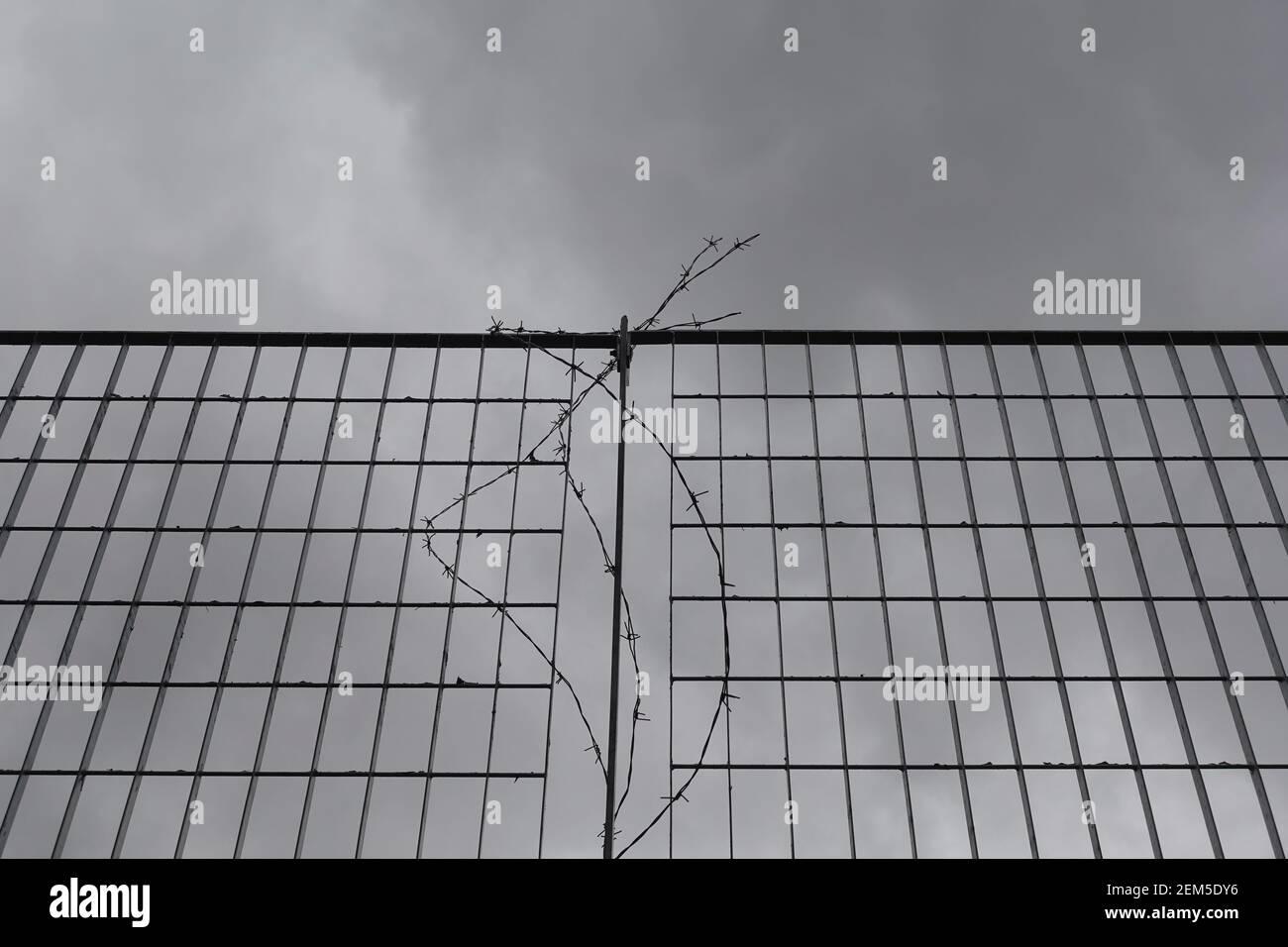Malla metálica y alambre de púas bajo cielo nublado. Foto de stock