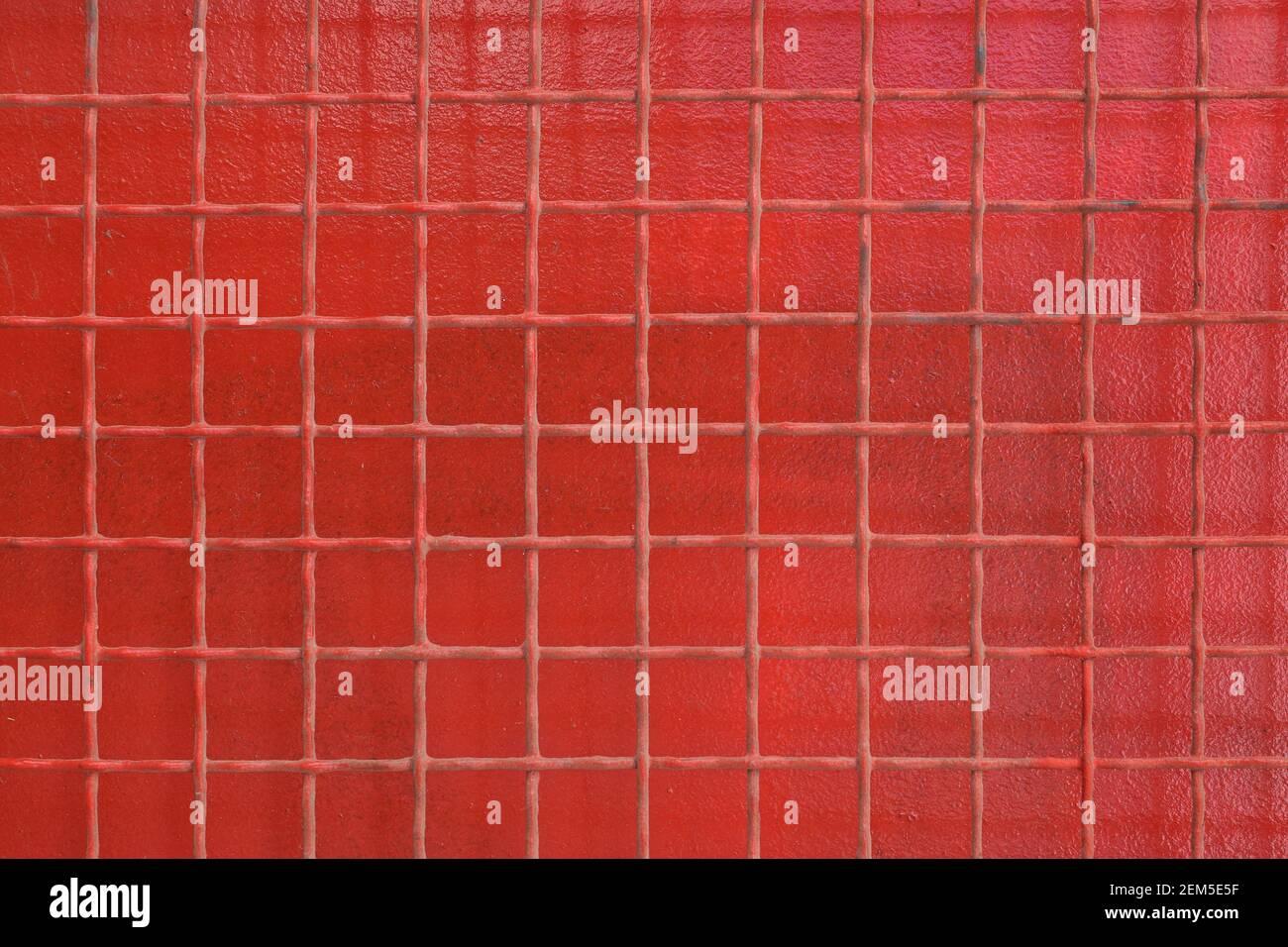 Rejilla de alambre de hierro oxidado cuadrados patrón sobre fondo de metal pintado de color rojo. Foto de stock