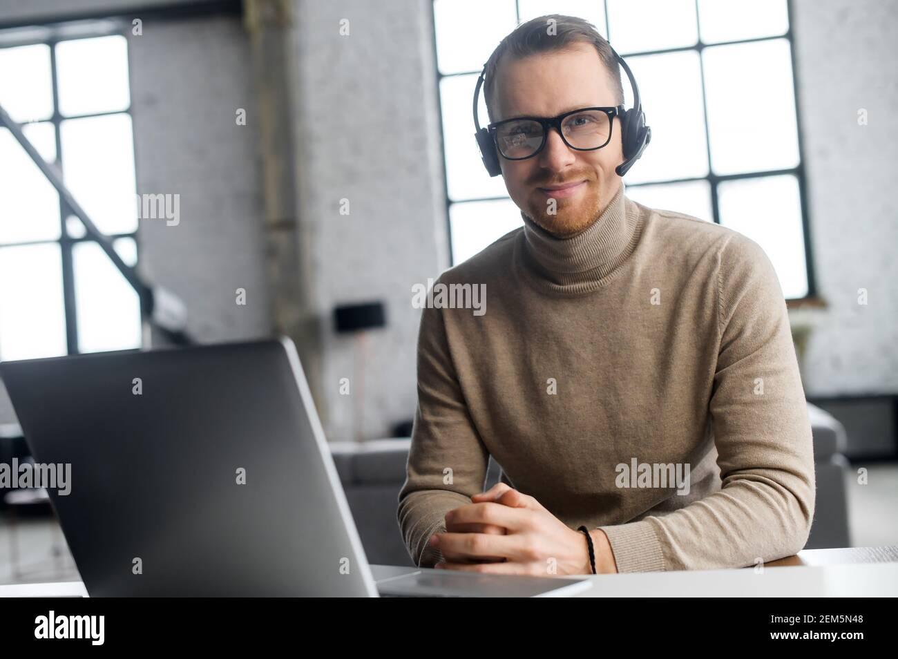 Un operador seguro con auriculares y gafas, mirando la cámara, sentado en el portátil, trabajador del año, disfruta de su trabajo, lugar de trabajo, escuchando al cliente atentamente, puede resolver su solicitud Foto de stock