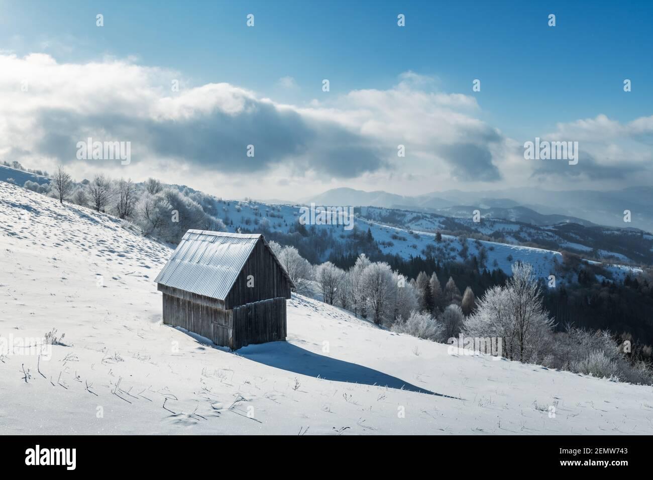Fantástico paisaje invernal con cabaña de madera en bosque nevado. Casa acogedora en las montañas de los Cárpatos. Navidad concepto de vacaciones Foto de stock