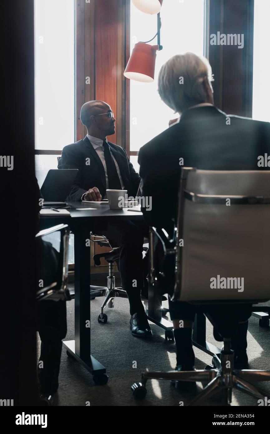 Hombres profesionales mirando fuera mientras que se sentaba en la mesa de la conferencia adentro sala de juntas durante la reunión Foto de stock
