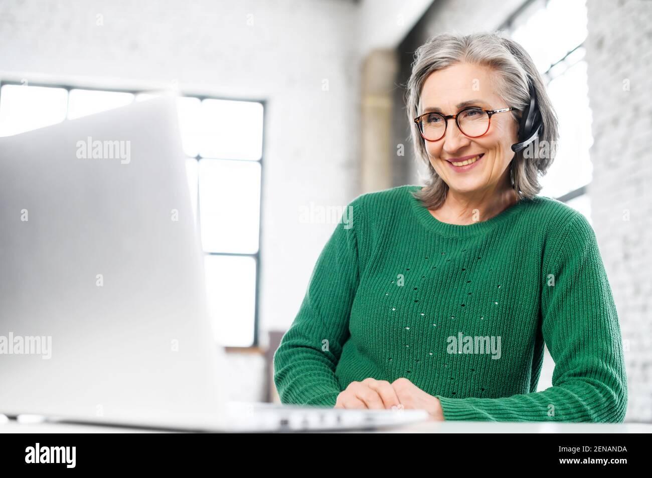 Alegre mujer anciana con auriculares, arrugas en la cara, sonriendo, escuchando en el ordenador, consultando al cliente en línea, da el Consejo, el trabajo en casa, persona positiva, se toma cada oportunidad de trabajar Foto de stock