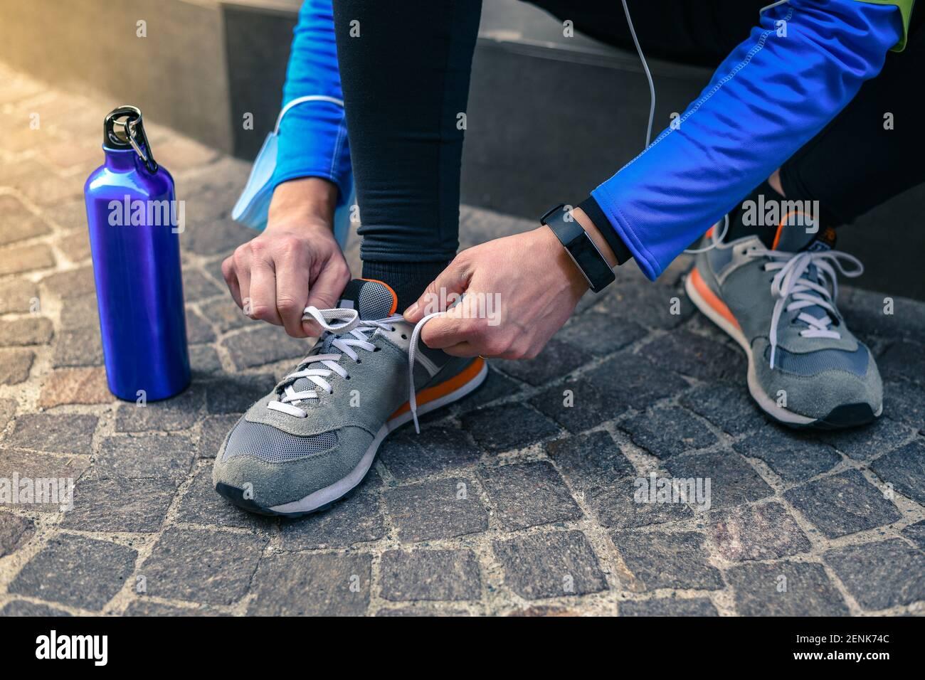 Varón atando sus zapatos de running escuchando música antes del entrenamiento. Hombre descansando durante el jogging. Corredor con teléfono móvil conectado a una grabación de reloj inteligente Foto de stock