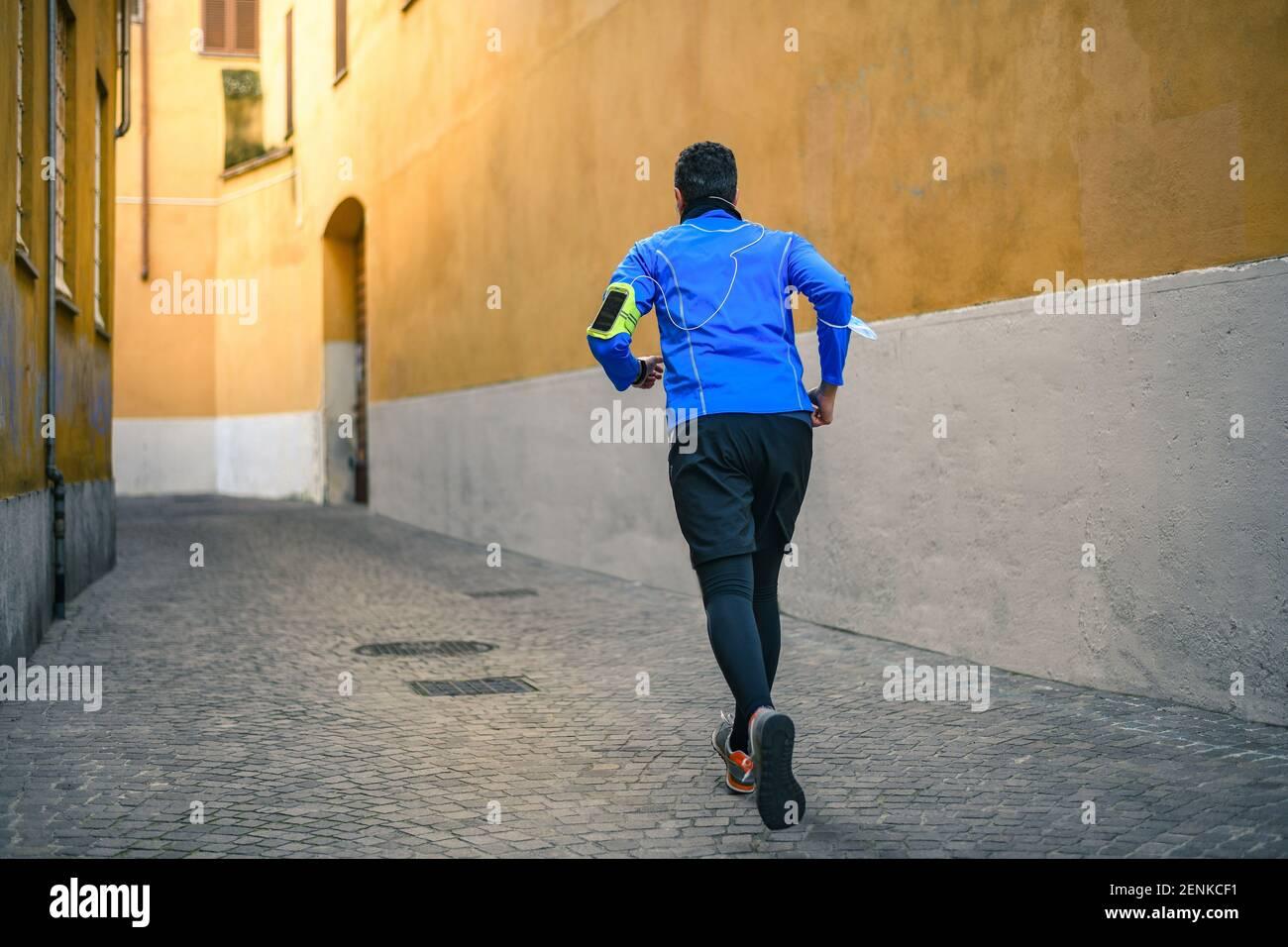 Hombre corriendo y escuchando música durante el entrenamiento. El hombre corre en la ciudad y jogging solo. Corredor con teléfono móvil conectado a una grabación de reloj inteligente Foto de stock