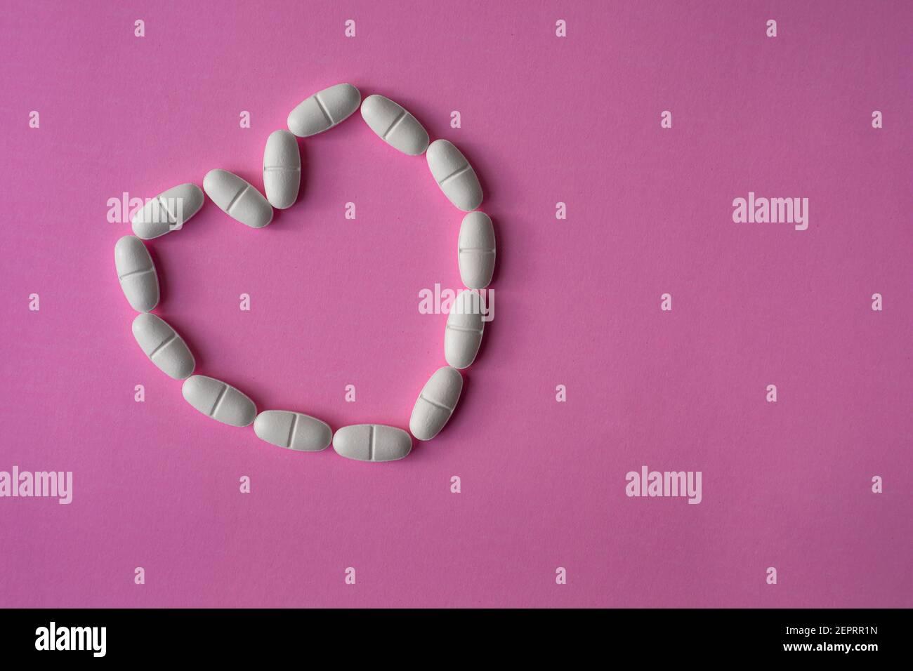 Pastillas o tabletas blancas y grandes, dispuestas en forma de corazón para representar la salud sobre fondo rosa Foto de stock