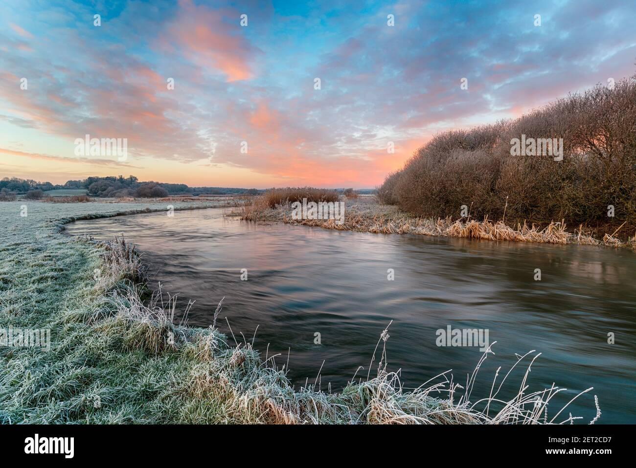 Un amanecer de invierno helado sobre el río Frome en Holmebridge Entre lana y Wareham en el campo de Dorset Foto de stock