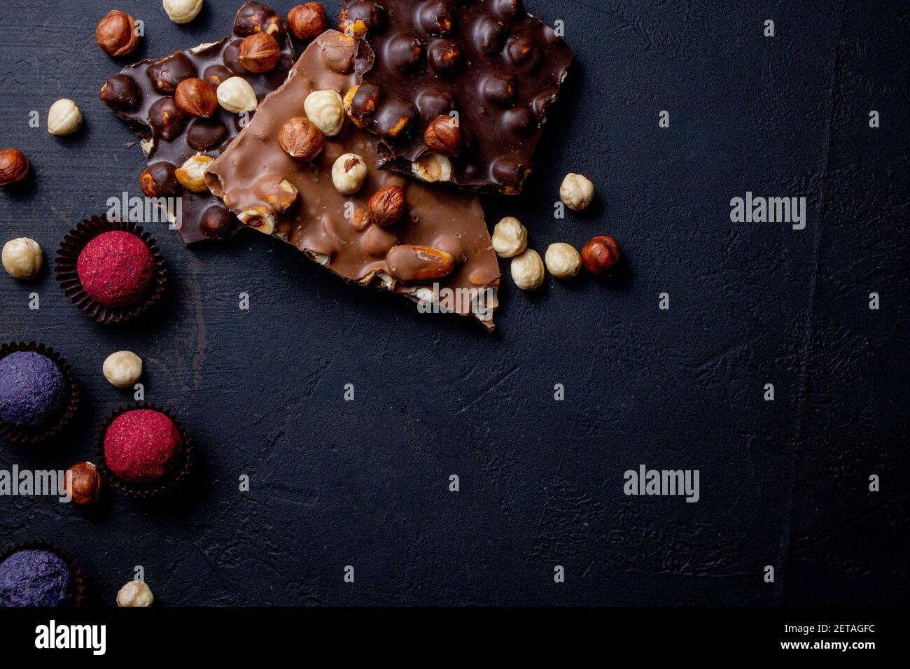 Trufa de chocolate con trozos de chocolate y polvo de cacao volador sobre un fondo oscuro Foto de stock