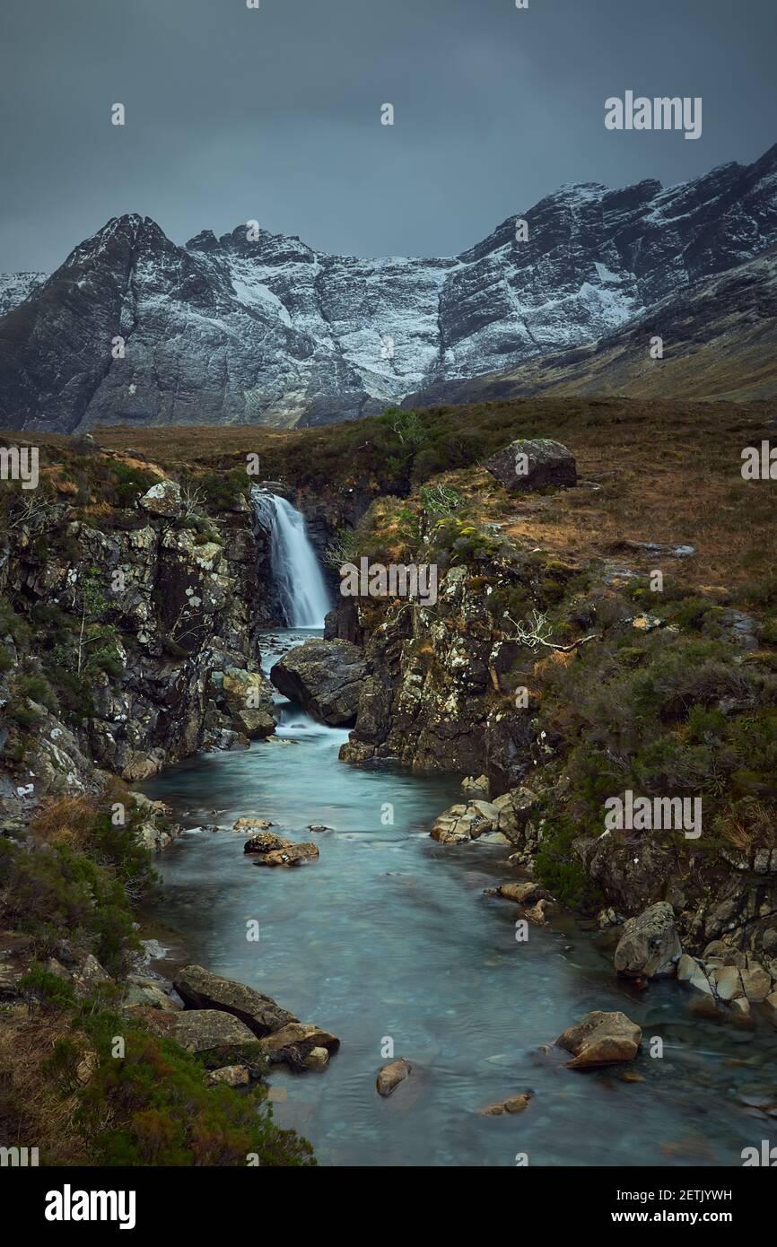 río con cascada en invierno, nieve y vegetación seca. Famoso destino turístico - piscinas de hadas - Isla Skye - Escocia - Reino Unido Foto de stock