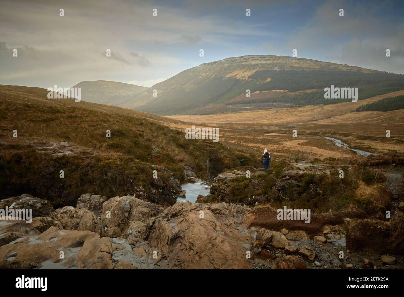 Montañero turístico mirando las impresionantes vistas en el valle montañoso.concepto de viaje, turismo Fairy Pools Skye Island - Escocia Foto de stock