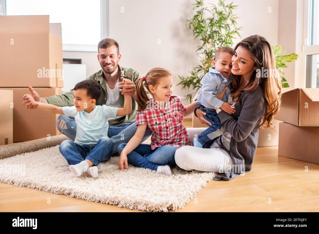 Recién se mudó en familia relajándose en casa nueva mientras hacía un descanso Foto de stock
