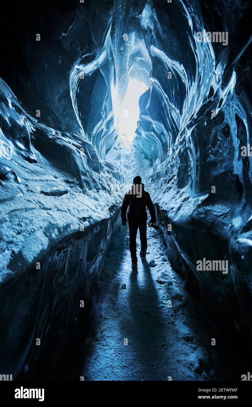 Silueta del hombre explorando una increíble cueva de hielo glacial Las montañas de Kazajstán Foto de stock