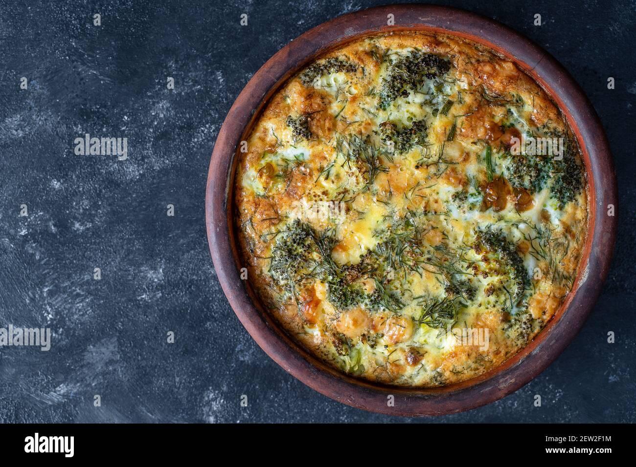 Cuenco de cerámica con frittata vegetal, comida vegetariana simple. Frittata con huevo, pimienta, cebolla, brócoli y queso sobre mesa de madera, primer plano. Italiano Foto de stock