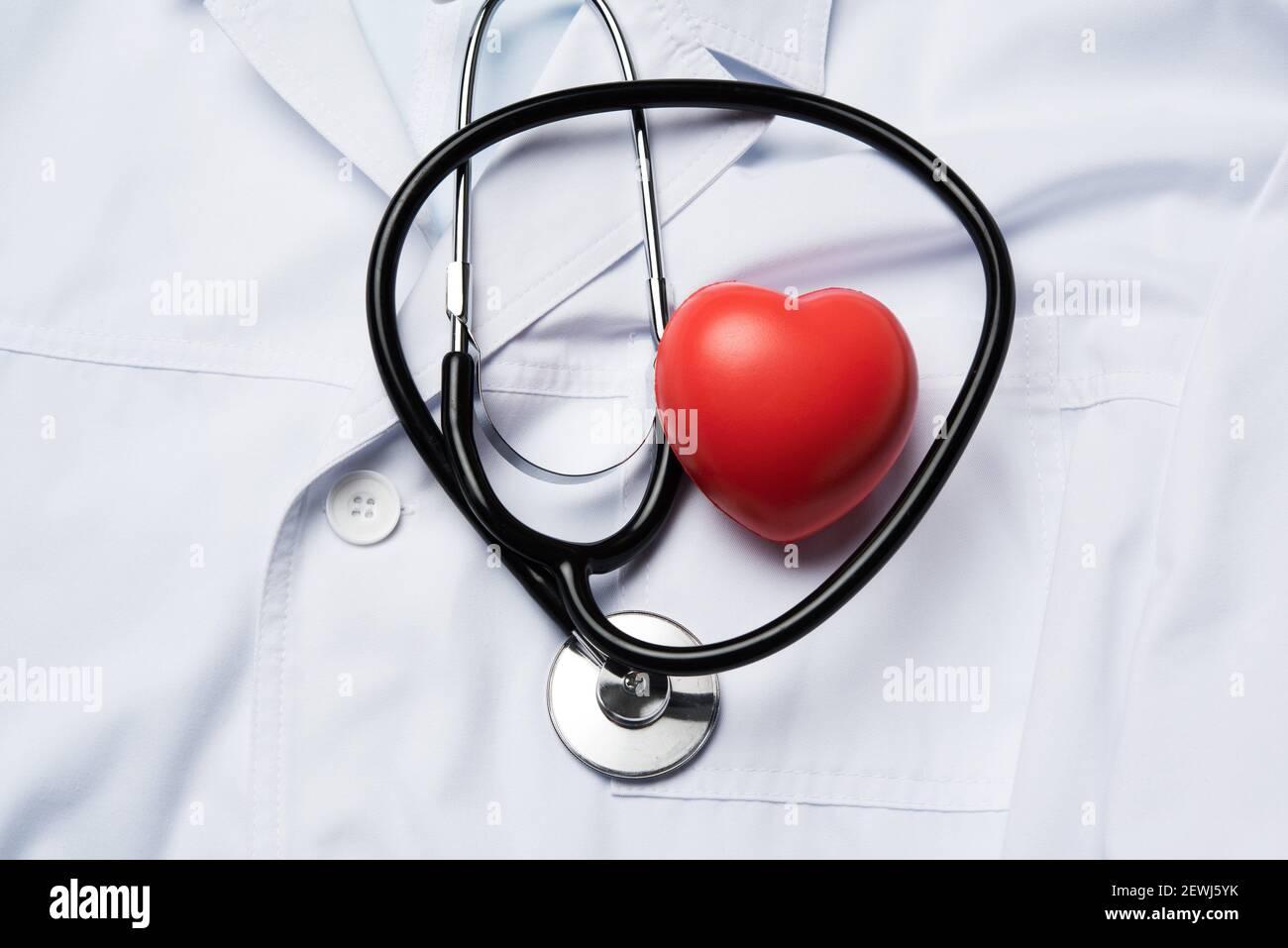 estetoscopio médico y corazón de caucho rojo sobre fondo blanco, vista superior. Foto de stock