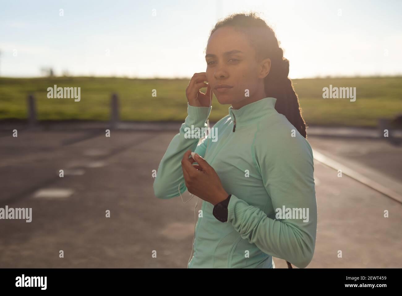 Mujer afroamericana que se concentra, llevando ropa deportiva haciendo ejercicio en el parque poniendo auriculares Foto de stock
