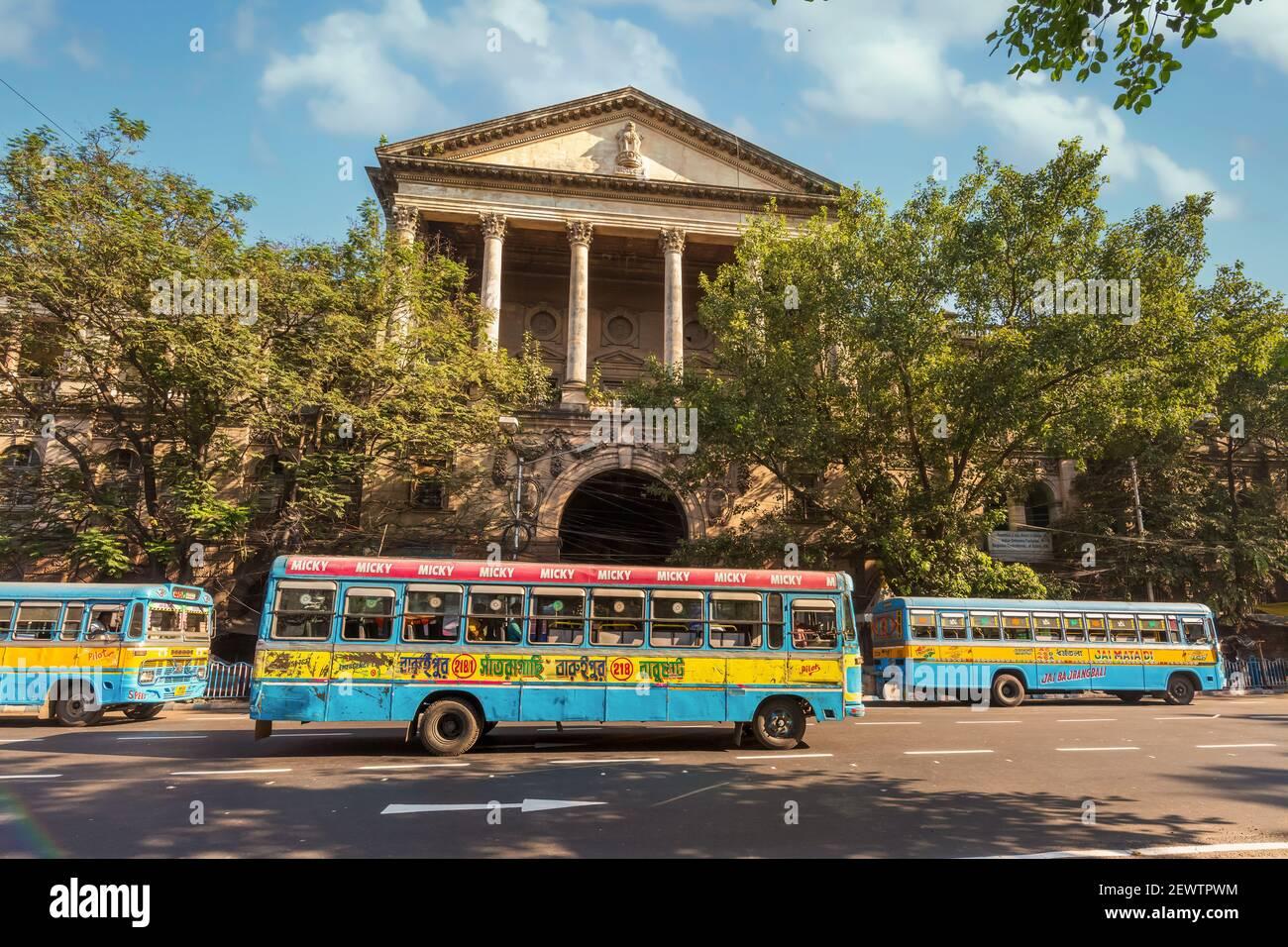 Autobuses de transporte público en la carretera de la ciudad frente a la antigua Patrimonio edificio del Gobierno en la zona de Dalhousie de Kolkata Foto de stock