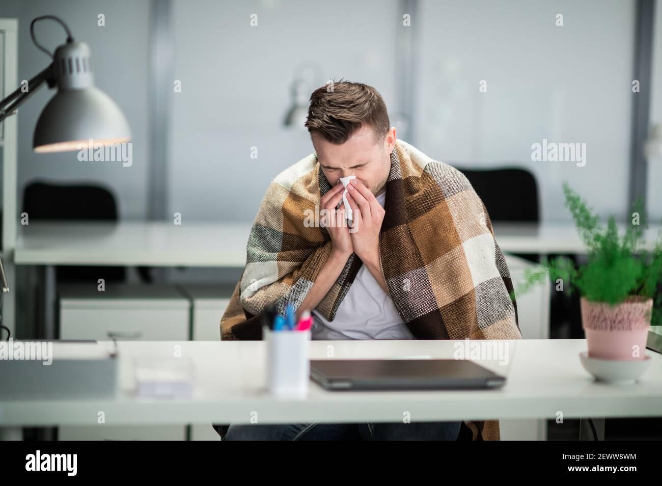 Durante la pandemia, el gerente se resfrío y tiene una nariz muy mocosa Foto de stock