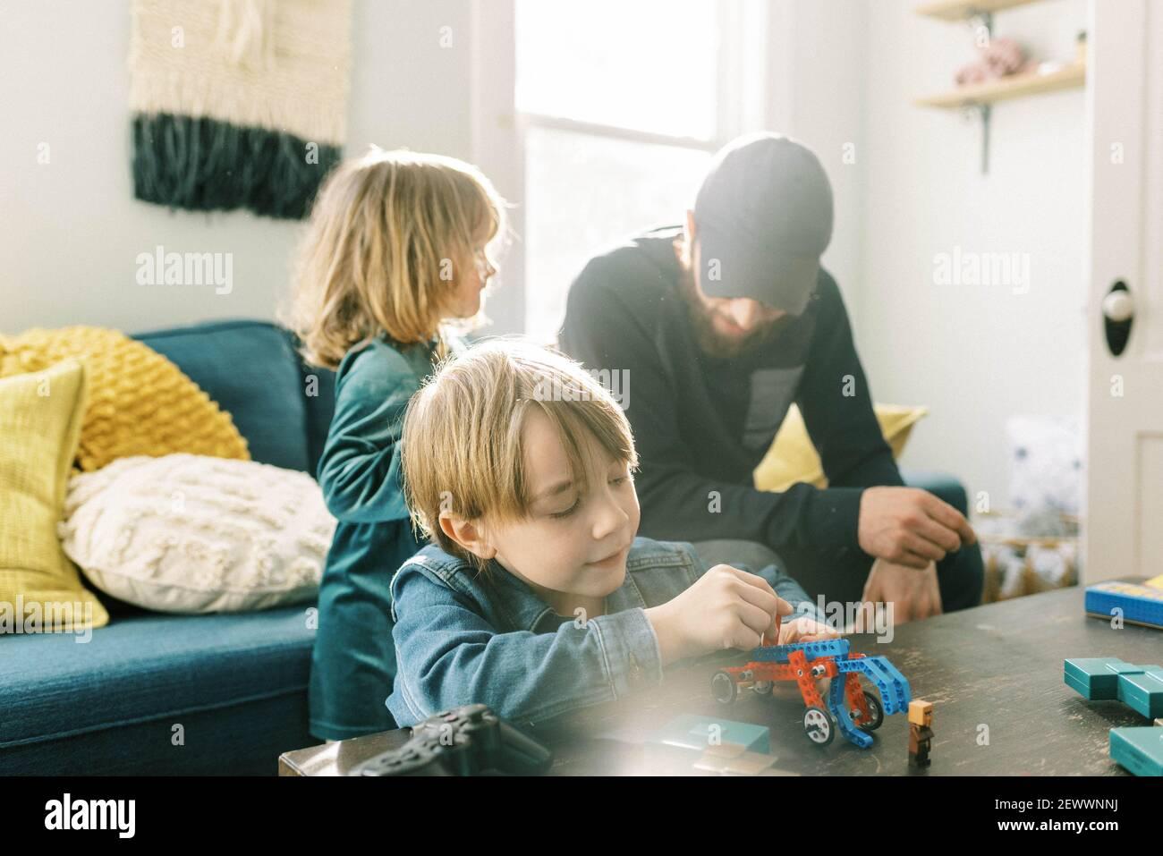 un pequeño y experto jugando con juguetes de construcción en la familia habitación Foto de stock