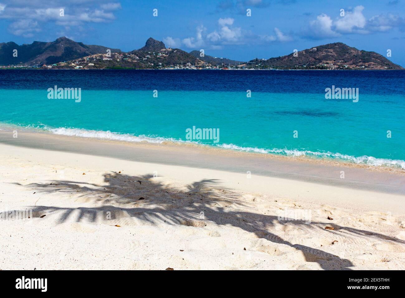 La sombra de las palmeras en una playa caribeña con el océano Turquesa del Caribe y la isla Union: Playa Casuarina, Isla Palm, San Vicente y las Granadinas Foto de stock
