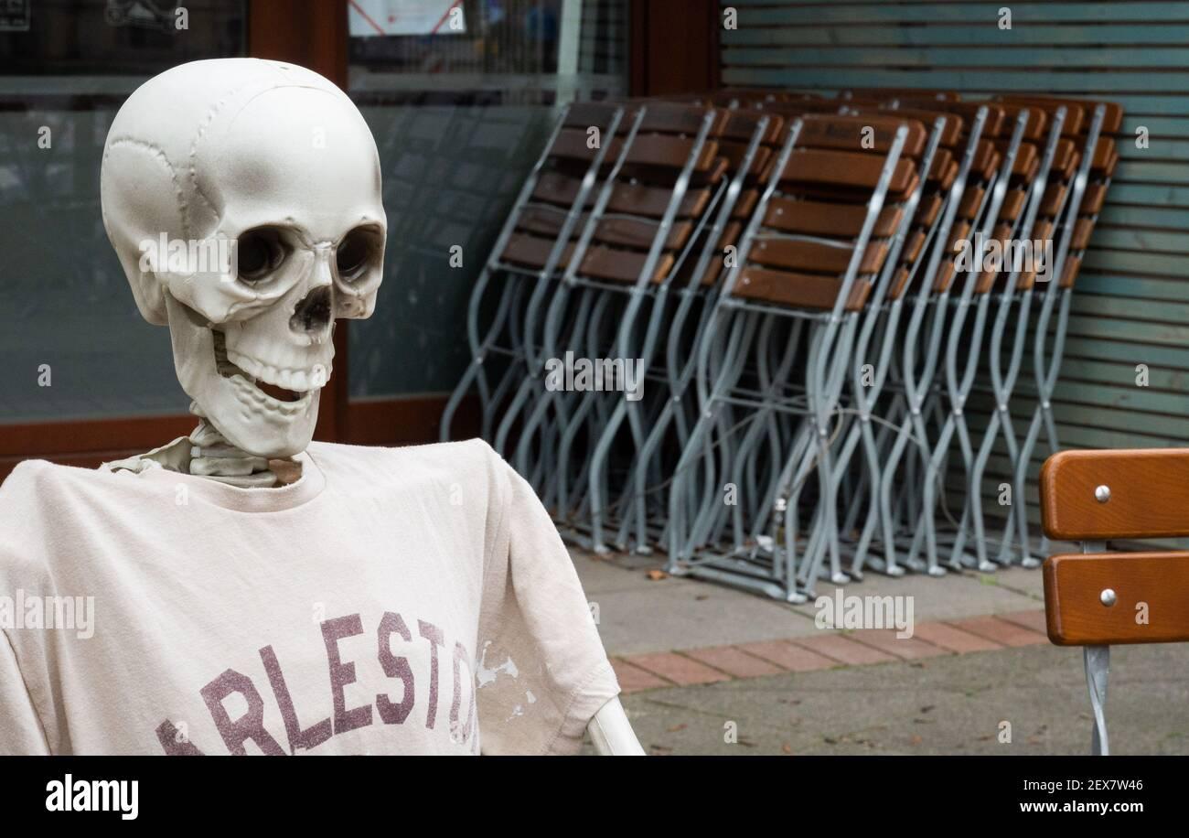 04 de marzo de 2021, Baja Sajonia, Hanover: Un esqueleto se encuentra fuera de un restaurante cerrado debido a la pandemia de Corona en Südstadt. El bloqueo en Alemania se extiende hasta marzo de 28. Foto: Julian Stratenschulte/dpa Foto de stock