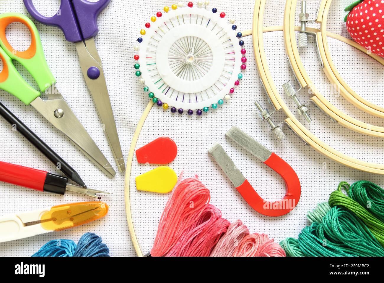 aro de bordado con accesorio de costura, tijeras, hilos de bordado y aguja sobre una tela blanca Foto de stock