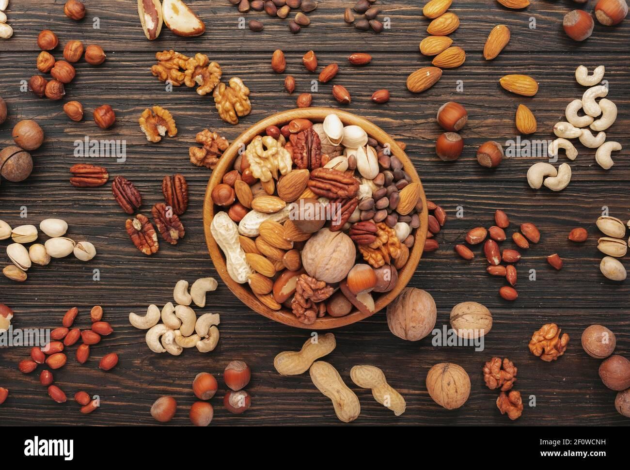 Surtido de frutos secos en cuencos. Anacardos, avellanas, nueces, pistachos, pacanas, nueces de pino, cacahuetes, macadamia, almendras, nueces de brasil. Mezcla de alimentos en madera Foto de stock