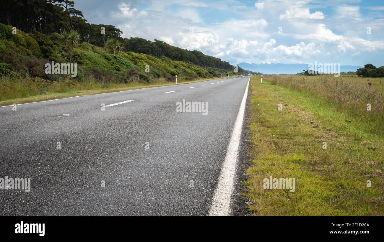 Camino que conduce a la distancia (horizonte recto). Tiro hecho durante el día soleado en la región de la costa oeste de Nueva Zelanda Foto de stock